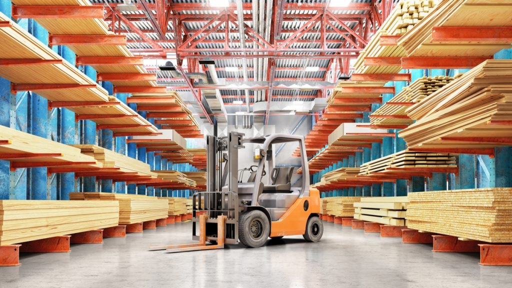 A forklift in a warehouse full of different types of plywood