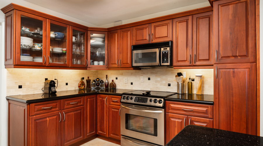 A beautifully stained kitchen of cherry wood cabinets
