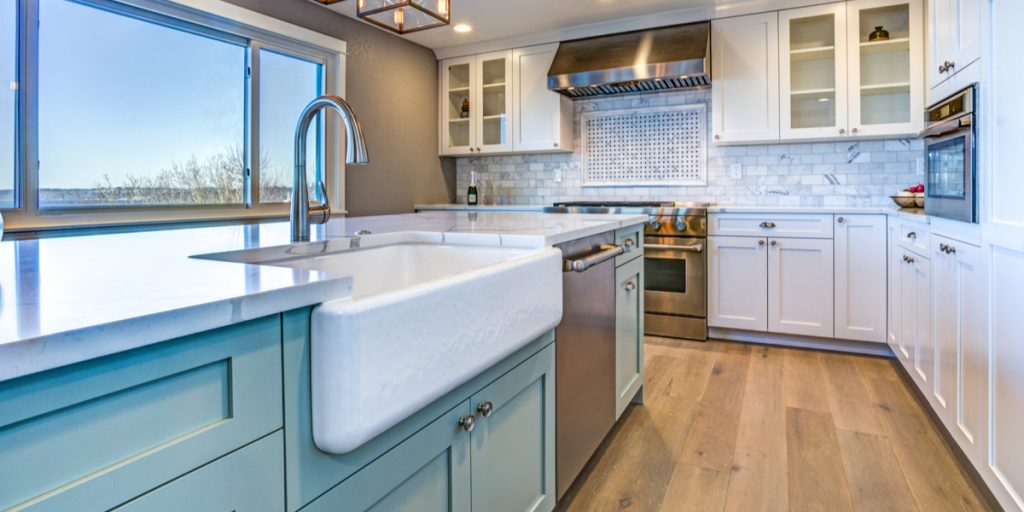Farmstyle kitchen with white cabinets, light blue island with apron sink