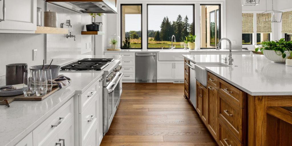 White kitchen cabinets with hardwood flooring and wood island