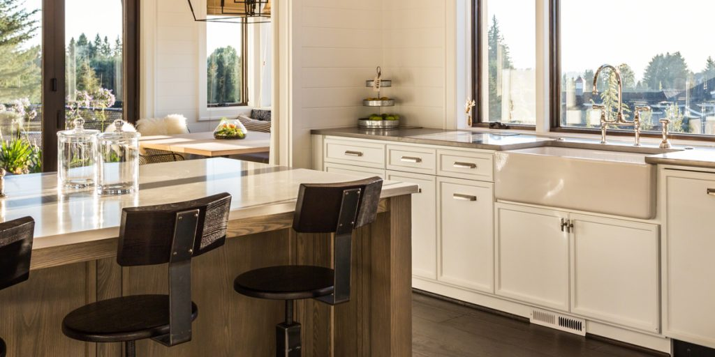 Kitchen with off white cabinets, apron sink and natural wood island.